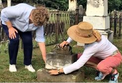 Two women inspecting a grave stone.
