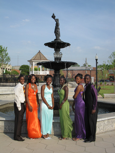 Young couples in formal attire pose for a picture in front of Cooke Fountain.